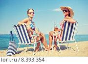 Купить «happy women sunbathing in lounges on beach», фото № 8393354, снято 26 июля 2014 г. (c) Syda Productions / Фотобанк Лори
