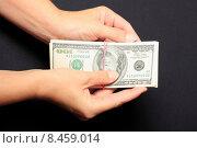 Купить «Пачка американских долларов, перетянутая резинкой в руках на черном фоне», эксклюзивное фото № 8459014, снято 28 июля 2015 г. (c) Яна Королёва / Фотобанк Лори