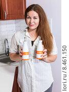 Купить «Женщина на кухне держит в руках керамические емкости для растительного масла и уксуса», фото № 8461150, снято 27 июля 2015 г. (c) Кекяляйнен Андрей / Фотобанк Лори