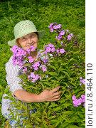 Купить «Пожилая женщина улыбается и обнимает куст садовых сиреневых флоксов на дачном участке ясным солнечным днём», фото № 8464110, снято 26 июля 2015 г. (c) Максим Мицун / Фотобанк Лори