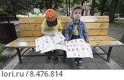Купить «Дети сидят на лавочке и наклеивают в книгу наклейки», эксклюзивный видеоролик № 8476814, снято 22 июля 2015 г. (c) Алексей Бок / Фотобанк Лори
