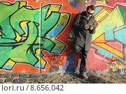 Купить «man outside wall stand reads», фото № 8656042, снято 18 февраля 2020 г. (c) PantherMedia / Фотобанк Лори