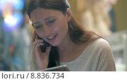 Купить «Женщина говорит по телефону с планшетом в руках находясь в кафе», видеоролик № 8836734, снято 7 июля 2015 г. (c) Данил Руденко / Фотобанк Лори