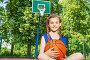 Улыбающаяся девочка сидит с мячом на баскетбольной площадке, фото № 9105554, снято 3 июня 2015 г. (c) Сергей Новиков / Фотобанк Лори