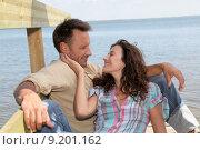 Купить «Closeup of loving couple sitting on a pontoon by a lake», фото № 9201162, снято 20 января 2019 г. (c) PantherMedia / Фотобанк Лори