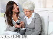 Young woman showing how to use mobile phone to grandmother. Стоковое фото, фотограф Fabrice Michaudeau / PantherMedia / Фотобанк Лори
