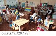 Купить «Игровая комната в детском садике с воспитателем за столом и группой дошкольников, играющих на полу», видеоролик № 9720178, снято 10 июня 2015 г. (c) Кекяляйнен Андрей / Фотобанк Лори