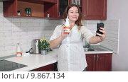 Купить «Домохозяйка делает селфи на мобильный телефон на кухне с кухонными принадлежностями в руках», видеоролик № 9867134, снято 5 августа 2015 г. (c) Кекяляйнен Андрей / Фотобанк Лори