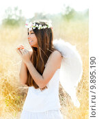Купить «Angel girl in golden field with feather white wings», фото № 9895190, снято 19 июня 2018 г. (c) PantherMedia / Фотобанк Лори