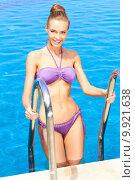 Купить «Cute woman standing on pool ladder», фото № 9921638, снято 24 апреля 2019 г. (c) PantherMedia / Фотобанк Лори