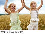 Купить «Portrait of energetic twin sisters jumping in wheat field and having fun», фото № 9989330, снято 21 июля 2019 г. (c) PantherMedia / Фотобанк Лори