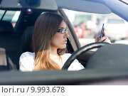 Купить «Confident woman dialing phone number while sitting in car», фото № 9993678, снято 16 октября 2019 г. (c) PantherMedia / Фотобанк Лори
