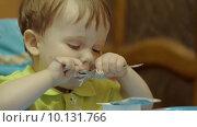Купить «Cute boy having meal on his own», видеоролик № 10131766, снято 6 августа 2015 г. (c) Данил Руденко / Фотобанк Лори