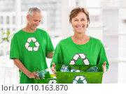 Smiling eco-minded woman holding recycling box. Стоковое фото, агентство Wavebreak Media / Фотобанк Лори