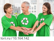 Smiling eco-minded colleagues putting hands together. Стоковое фото, агентство Wavebreak Media / Фотобанк Лори