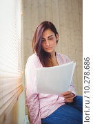 Купить «Pretty brunette reading documents beside window», фото № 10278686, снято 4 июня 2015 г. (c) Wavebreak Media / Фотобанк Лори