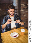 Купить «Handsome man taking a picture of his cake and coffee», фото № 10298502, снято 24 апреля 2015 г. (c) Wavebreak Media / Фотобанк Лори