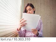 Купить «Pretty brunette reading documents beside window», фото № 10303310, снято 4 июня 2015 г. (c) Wavebreak Media / Фотобанк Лори