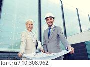 Купить «smiling businessmen with blueprint and helmets», фото № 10308962, снято 19 августа 2014 г. (c) Syda Productions / Фотобанк Лори