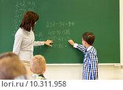 schoolboy with math teacher writing on chalk board. Стоковое фото, фотограф Syda Productions / Фотобанк Лори