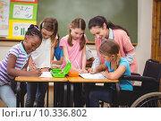 Купить «Teacher and pupils working at desk together», фото № 10336802, снято 7 июля 2015 г. (c) Wavebreak Media / Фотобанк Лори
