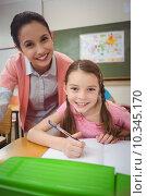 Купить «Pupil and teacher at desk in classroom», фото № 10345170, снято 7 июля 2015 г. (c) Wavebreak Media / Фотобанк Лори