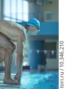Купить «Happy muscular swimmer wearing glasses and cap at swimming pool and represent health and fit concept», фото № 10346210, снято 27 июня 2019 г. (c) PantherMedia / Фотобанк Лори