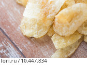 Купить «close up of crunchy potato crisps on wooden table», фото № 10447834, снято 22 мая 2015 г. (c) Syda Productions / Фотобанк Лори