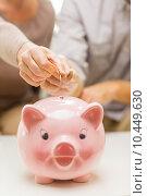 Купить «close up of hands putting coin money to piggy bank», фото № 10449630, снято 4 сентября 2014 г. (c) Syda Productions / Фотобанк Лори