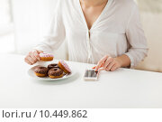 Купить «close up of hands with smart phone and donuts», фото № 10449862, снято 21 мая 2015 г. (c) Syda Productions / Фотобанк Лори