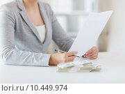 close up of female hands with money and tax report, фото № 10449974, снято 2 июля 2015 г. (c) Syda Productions / Фотобанк Лори