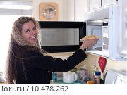 Купить «woman puts food in oven», фото № 10478262, снято 23 апреля 2018 г. (c) PantherMedia / Фотобанк Лори