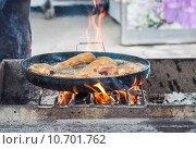Купить «Приготовление рыбы на открытой жаровне печи-гарнушки в станице Старочеркасская Ростовской области», эксклюзивное фото № 10701762, снято 15 июля 2015 г. (c) Алёшина Оксана / Фотобанк Лори