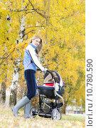 Купить «woman with a pram on walk in autumnal alley», фото № 10780590, снято 26 марта 2019 г. (c) PantherMedia / Фотобанк Лори