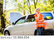 Купить «Young female driver wearing a high visibility vest, calling the roadside service/assistance after her car has broken down», фото № 10984654, снято 26 июня 2019 г. (c) PantherMedia / Фотобанк Лори