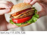 Купить «Мужские руки держат гамбургер», фото № 11070726, снято 21 августа 2015 г. (c) Лидия Рыженко / Фотобанк Лори