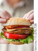 Купить «Мужские руки держат бургер», фото № 11070738, снято 21 августа 2015 г. (c) Лидия Рыженко / Фотобанк Лори