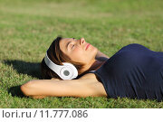 Купить «Relaxed woman listening to the music with headphones lying on the grass», фото № 11777086, снято 20 сентября 2019 г. (c) PantherMedia / Фотобанк Лори