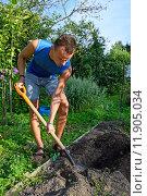 Купить «Молодой мужчина копает грядку на приусадебном участке в солнечный день», фото № 11905034, снято 5 августа 2015 г. (c) Максим Мицун / Фотобанк Лори