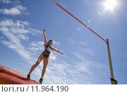 Купить «Young female athlete preparing to jump over bar, low angle view (lens flare)», фото № 11964190, снято 17 августа 2018 г. (c) PantherMedia / Фотобанк Лори