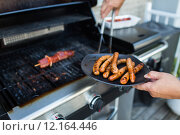 Купить «BBQ with sausages and red meat on the grill - male hands holding a plate and taking the meat off the grill before it is too late», фото № 12164446, снято 4 августа 2020 г. (c) PantherMedia / Фотобанк Лори