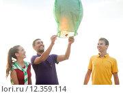 Купить «happy friends with chinese sky lantern on beach», фото № 12359114, снято 31 августа 2013 г. (c) Syda Productions / Фотобанк Лори