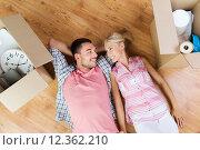 Купить «happy couple lying on floor among cardboard boxes», фото № 12362210, снято 6 июня 2015 г. (c) Syda Productions / Фотобанк Лори
