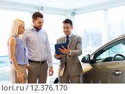 happy couple with car dealer in auto show or salon. Стоковое фото, фотограф Syda Productions / Фотобанк Лори