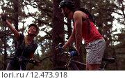 Купить «Couple biking through a forest», видеоролик № 12473918, снято 15 октября 2019 г. (c) Wavebreak Media / Фотобанк Лори