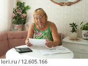 Купить «Пенсионерка в очках с квитанциями на оплату», фото № 12605166, снято 15 августа 2015 г. (c) Ирина Новак / Фотобанк Лори