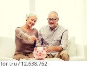 Купить «senior couple with money and piggy bank at home», фото № 12638762, снято 4 сентября 2014 г. (c) Syda Productions / Фотобанк Лори