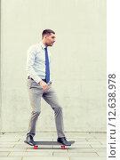 Купить «young smiling businessman with skateboard outdoors», фото № 12638978, снято 19 августа 2014 г. (c) Syda Productions / Фотобанк Лори