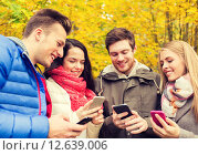 Купить «smiling friends with smartphones in city park», фото № 12639006, снято 4 октября 2014 г. (c) Syda Productions / Фотобанк Лори
