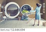 Купить «Женщина стоит перед большой стиральной машиной», фото № 12644694, снято 5 июля 2020 г. (c) Виктор Застольский / Фотобанк Лори